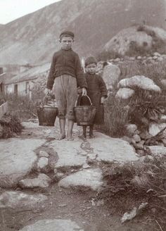 Two boys standing in the village on the Island of Hirta in the St. Kilda archipelago in the Western Isles of Scotland. Names/Date/Photographer - Unknown. St Kilda Scotland, Old Photos, Vintage Photos, Scotland People, Ireland Country, Scotland History, Diary Covers, Outer Hebrides, Scottish Islands