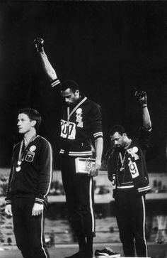 American sprinters Tommie Smith (center) and John Carlos (right), after winning gold and bronze Olympic medals in the 200m, respectively, raise their fists in a Black Power salute, Mexico, 1968. Australian silver medalist Peter Norman is at left.