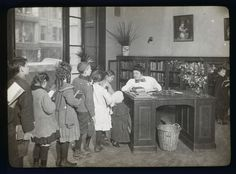 Children lined up at the Chatham Square Branch librarian's desk, 1910.