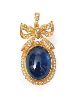 A sapphire diamond pendant with ornaments of bows  18 ct. yellow gold. The oval shaped sapphire cabochon of deep blue colou