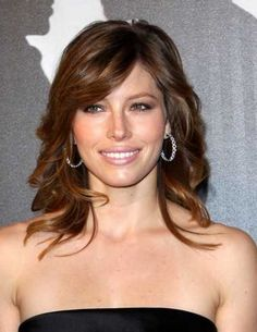 This medium-length wavy layered hair cut with side bangs is gorgeous.