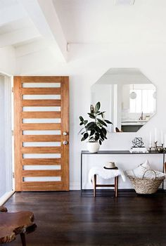 Oak Front Door with rectangular cut outs | Large Unframed Octagonal Wall Mirror | Dark Stained Hardwood Floors | White Walls
