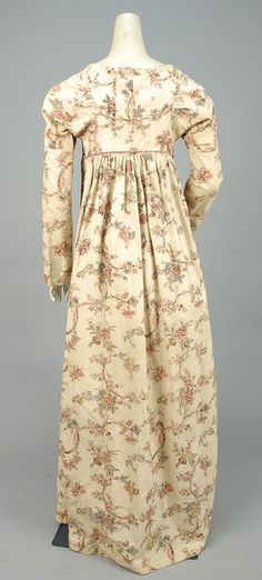 Cream with scrolling polychrome floral having long sleeve, gathered bodice, high waist with belt loops, flared skirt pieced side gores, muslin bodice lining with front closure. B-32, high W-34, L-53. (Fading and period repairs to shoulder area, light stains, later non-conforming braided wool tie) good. LACMA. - whitakerauction