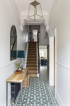 Interior Design & Styling in this large 5 bedroom Victorian house by Imperfect Interiors www.imperfectinteriors.co.uk. Wood & metal console, metal framed mirror, Pooky brass lanterns, black column radiator & Victorian tiles against a backdrop of warm but pale grey walls in the entrance hallway . Photos by Chris Snook