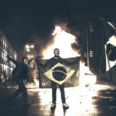 This June 17, 2013 photo, a demonstrator holds a Brazilian flag in front of a burning barricade during a protest in Rio de Janeiro in Rio de Janeiro, Brazil. Protesters massed in at least seven Brazilian cities for another round of demonstrations voicing disgruntlement about life in the country, raising questions about security during big events like the current Confederations Cup and a papal visit next month. (AP Photo/Felipe Dana, File)