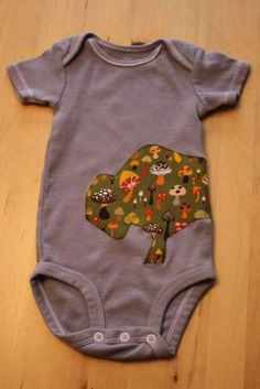 Onesies made at our baby shower. Iron on an adhesive backing (I used Heat N'Bond) to your favorite fabrics, create and cut out a design, iron onto onesie, and (later) zig zag stitch all the way around. Take a photo of the 'designer' so you can send them one of your baby in the onesie once he/she's born.