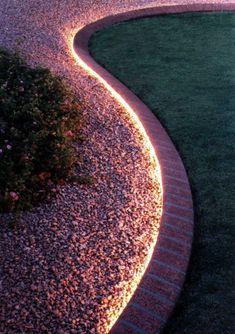 Eine wundervolle Idee: Der kleine Vorsprung zwischen Garten und Kiesweg wird mit einem Lichtband hervorgehoben.