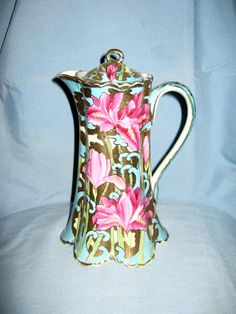 Stunning, vibrantly hand painted Nippon skirted bottom chocolate pot with fuchsia florals and robin egg blue back ground. Gold moriage (raised hand painted dots) and golden enamel painting finish off this beautifully decorated piece.
