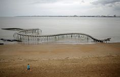 """A boy runs in front of the """"Serpent d'ocean"""" (Ocean snake) in Saint-Brevin-les-Pins, western France, April Ocean Serpent is a giant aluminium sea serpent skeleton by the Chinese artist Huang Yong Ping. (Photo by Stephane Mahe/Reuters) Avant Garde Artists, Sea Serpent, Land Art, Surreal Art, Art Therapy, Art World, Surrealism, Chinese, Skeleton"""