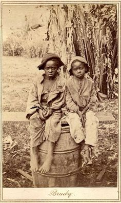 A haunting 150-year-old photo found in a North Carolina attic shows a young black child named John, barefoot and wearing ragged clothes, perched on a barrel next to another unidentified young boy.    In April, the photo was found at a moving sale in Charlotte, accompanied by a document detailing the sale of John for $1,150, not a small sum in 1854.
