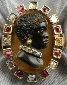 Antique Blackamoor Cameo Ring In 14k Gold Mount, The Hardstone Cameo With Figure In Profile Wearing An Old Mine-Cut Diamond Collar And Gold Bead Earring, The Gold Frame With Box-Set Cushion And Circular-Cut Rubies And Rose-Cut Diamonds, Joined To A Later Gold Shank With Engraved Shoulders   c.1801-1912  -  Prices4Antiques