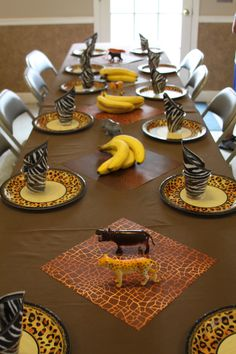 Safari table setting: Brown Twin Sheets, Animal Print Plates and Napkins, Animal Print Scrapbook Paper (use later for birthday scrap-booking), Banana's and Plastic Animals (extra treats for kiddos to take home).
