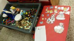 Ontdektafel pakjes met de post: we maken allerlei pakjes, stoppen die in een doosje, wegen die en noteren welk materiaal er het meest weegt. Op de rode tafel leggen we de juiste pakjes terug bij de juiste postzak
