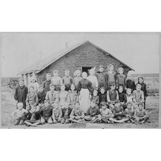 Teacher and Children in Front of Schoolhouse