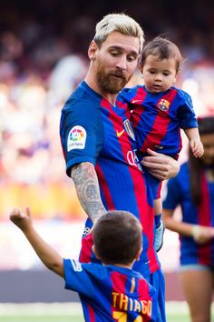 Lionel Messi of FC Barcelona carries his son Mateo Messi as he speaks to his son Thiago Messi before the La Liga match between FC Barcelona and Real Betis Balompie at Camp Nou on August 20, 2016 in Barcelona, Catalonia.