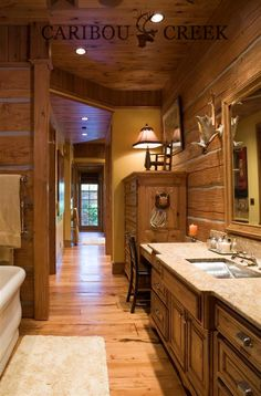 Beautiful Dovetail Log Master Bathroom with anter accents. This cozy walk through bathroom is a perfect use of space.  #CaribouCreekLogHomes #interiorloghomedesign