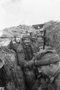 Men of 'C' Company, 1st Battalion, Cameronians (Scottish Rifles) in the trenches at Houplines during December 1914. They are sporting woolen watch caps that could be made to look like the fez (man with rifle, partially obscured in foreground).