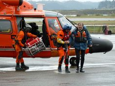 - A Coast Guard Dolphin helicopter crewmember from Group/Air Station North Bend escorts a survivor to awaiting EMS at Air Station North Bend. Coast Guard Rescue Swimmer, Us Coast Guard, Military Jobs, Aviation, Monster Trucks, North Bend, Army, Helicopters, Moth