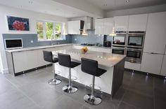 Kitchen island in Gloss White Nolte Lux Kitchen with Oak Smoky Silver Panels, enhanced with metallic blue glass splash backs.