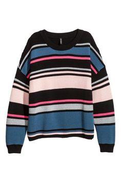 Een wijde trui van zachte, ribgebreide kwaliteit waarin glittergaren is verwerkt. De trui heeft een geribde boord langs de halsopening en onder aan de mouwe