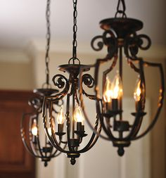 Three wrought iron hanging pendant light fixtures.