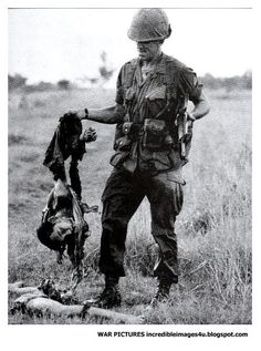 A U.S. soldier holds the remains of a dead Viet Cong