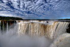 Garganta do Diabo, nas Cataratas do Iguaçú, no Parque Nacional Iguazú em Misiones, na Argentina. A altura das quedas varia de 40 a 80 metros. Dependendo da vazão do rio, o número de saltos varia, atingindo um número superior a 100 nos períodos de média vazão. A vazão média do rio fica em torno de 1.500 m³ por segundo, variando conforme o volume de chuvas. No conjunto são cerca de 275 quedas de água.  Fotografia: Roberto Peradotto no Flickr.