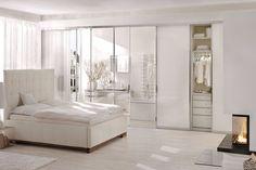 Sypialnia w bieli podkreślona listwami dekoracyjnymi NMC Arstyl w cieple kominka