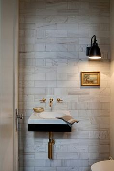 White and grey marble tile pops of gold faucets, exposed plumbing and artwork, with black sink undermount makes this powder room standout.