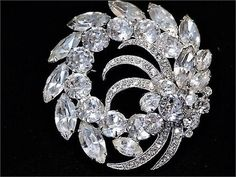 Item # 041723 (B-94)   Vintage late Art Deco early Mid Century, circa 1945-50 signed Eisenberg Ice Swarovski crystal glass rhinestone brooch set in rhodium plating.   Brooch measures approx 2 1/3 in diameter as it is not symmetrical, but rather a swirling layered and dimensional design.   Condition: Very good antique vintage condition with typical wear due to age and handling. All stones present and have a stunning clarity. Upon very close inspection there is one tip of one marquise nave...