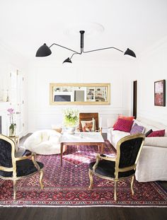 Bold living room with a red and magenta palette, grounded by black and gold…