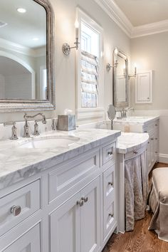Bathroom features light gray walls adorned with crisp white crown molding and base boards framing a drop-down skirted make up vanity topped with white and gray marble paired with gray linen vanity bench situated under window dress Home, Bedroom Interior, Grey Walls, Amazing Bathroom Remodels, White Bathroom, Amazing Bathrooms, White Bathroom Cabinets, Bathroom Design, Interior Design Bedroom