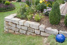 Mauersteine bieten sich auch optimal an, um ein Hochbeet an einer Hanglage anzulegen.