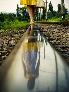 This photograph captures a contrast in texture and colors.  The rail captures the reflection of the girl to add a journey feeling.