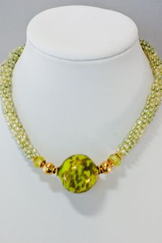 Spring is coming and this neckpiece is mindful of newly sprouting life. Its cheerful lime green coloration will make you smile. The beautiful 32 mm focal bead is another one from the late Shannon Hill
