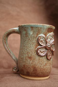 I love the dirty texture that the mug appears to have. I also love the pop out flower and the small swirl on the end of the handle that adds just a little more to the overall design