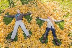 Older Caucasian couple playing in autumn leaves