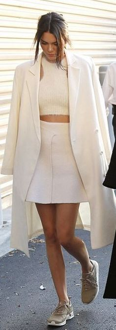 Kendall Jenner's white coat, wrap skirt, cropped top, and tan sneakers