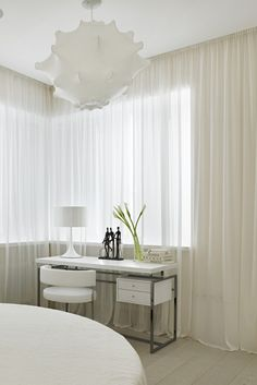 Thinking about some quick wall décor bedroom changes for above the bed? This small bedroom uses full wall curtains which add a nice touch to the space. The all white décor is also nicely contrasted by the off-white wood finished flooring.