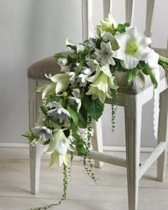 Easter Lilies Wedding Bouquet:Easter lilies tucked one inside the other make a surprising tiered silhouette, as if you've invented an entirely new species of flower. Like decadent floral drapery, this cascading bouquet of white lilies, clematis, campanula, and stephanotis vines falls and flows with the same graceful lines as the train of your gown.