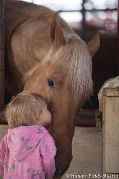 Little girl plants a kiss on a big horsey. Pretty big horse head, so gentle.