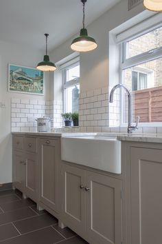 Kitchen with Belfast sink, cream units and grey marble worktop - White metro tiles with dark grout - green industrial pendant lampshades