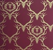 Deer Damask Eco Wallpaper - Claret/Antique Gold    Stag skulls and thistle in a damask-style repeat.     This eco wallpaper is printed at one of the few remaining print works in the Midlands on to PEFC accredited paper with water-based inks.      The Deer Damask range is printed using the traditional method of flexographic printing which uses less ink and produces a very smooth finish with crisp detail.     Roll Length: 10m  Roll Width: 68.5cm  Pattern Repeat: 61cm  Paper Weight: 150gsm…