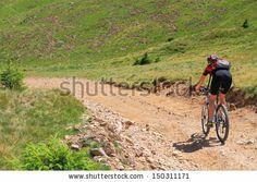 Mountain biker rides a bike on mountain trails - stock photo