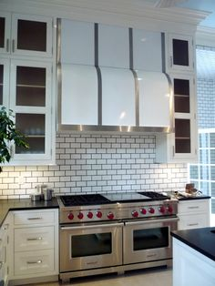 """English style kitchen cupboards with up to 10 foot ceiling height in River Oaks kitchen (Del Monte project).  60"""" Wolf dual fuel range, custom stainless & white range hood, subway tile with dark grout, high gloss lacquer on the cabinetry.  Designer: Miles Redd (NYC)"""