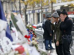Members of the band Eagles of Death Metal, Jesse Hughes, right, and Julian Dorio pay their respects to 89 victims who died in the Nov. 13 attacks in Paris at the Bataclan concert.   Jacques Brinon, AP