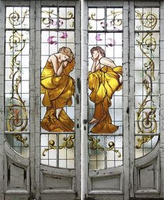 Art Nouveau style stained glass door, highlights faerie-like ladies in golden gowns.