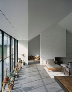 nice space. windows. white brick. stacked wood. plants in the window. chaise lounge.