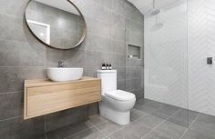Timber floating vanity with white round free standing basin. White cistern unit, chrome tap, chrome mixer, and chrome rain fall shower head. Large grey tiled walls. Project by - @carlandconstructions #taps #interiordesign #bathroom #australia #architecture #bathroomdesign #bathroomcollective Visit our website for more www.bathroomcollective.com.au