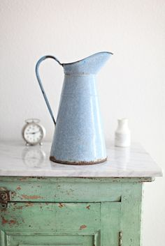 This is a beautiful light blue French enamelware pitcher.  It doesn't hold water, but can still be used as a vase to hold flowers  by adding a jar filled with water.  It also has small specks of white throughout the pitcher.